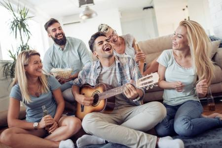 Group of friends having fun in living room in their home.Happy young people playing music with guitar,singing and laughing together .
