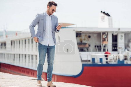 Young businessman is walking outside and using phone.Ship in the background.