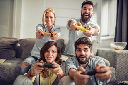 young friends having fun on couch with video game console