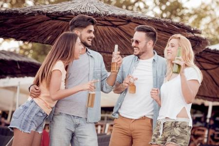 Photo for Friends drinking beers and having fun on beach party in evening - Royalty Free Image