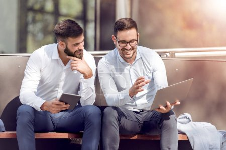 Photo for Two businessmen colleagues holding laptop and tablet and working together - Royalty Free Image
