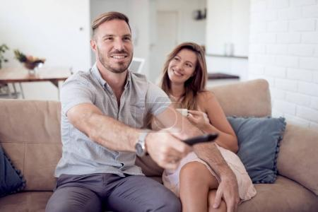 Loving couple watch TV and man switching channels