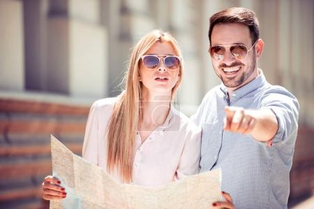 Traveling couple searching for next destination with map