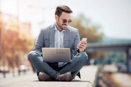 man sitting with legs crossed and using smartphone and laptop