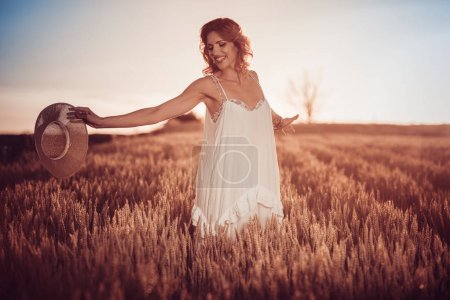 Young woman standing on wheat field with sunrise on background