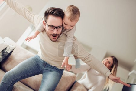 Photo for Happy family, mother and father playing with son at home - Royalty Free Image