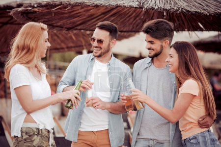 Group of best friends having fun on the beach with some cold beer,laughing and enjoying that beautiful moment together.