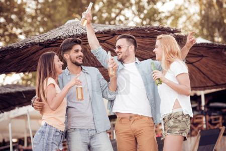 Photo for Friends drinking beers and having fun at beach party in evening. - Royalty Free Image