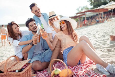 Group of happy young people having a picnic on the beach,having fun together. Everyone has a great mood.Summer time.