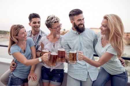 Group of young friends having fun at rooftop party, drinking beer and enjoying hot summer days.