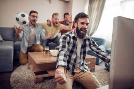 Friends watching football at home
