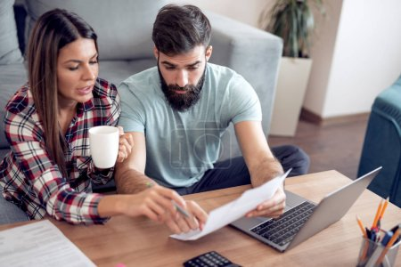young couple checking bills with laptop at home