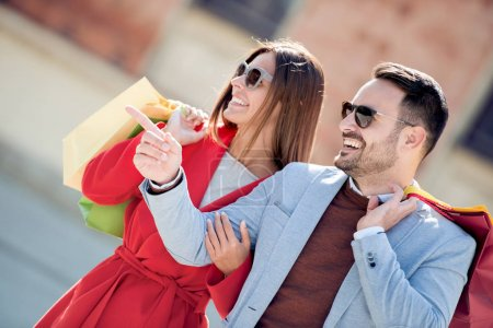 Photo for Young couple holding shopping bags after shopping - Royalty Free Image