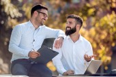 Two confident businessmen working on laptop in park