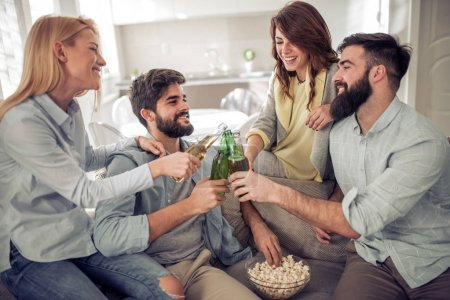 Cheerful group of friends drinking beer and eating popcorn at home