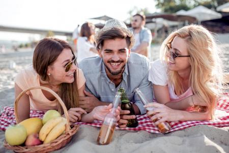 Three friends toasting with beer bottles outdoors.