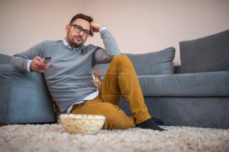 Photo pour Homme célibataire regardant la télévision, se détendre à la maison avec du pop-corn sur le sol . - image libre de droit