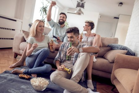 Photo for Group of adult friends having fun at home, playing video games, eating popcorn and drinking beer. - Royalty Free Image