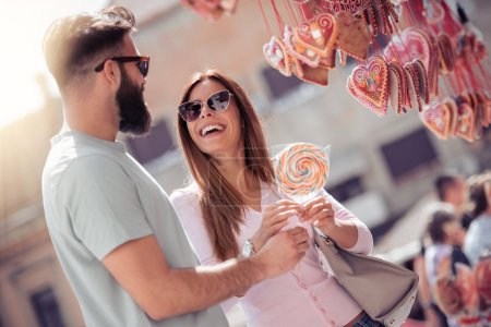 Happy smiling couple having fun outdoors,eating lollipop.