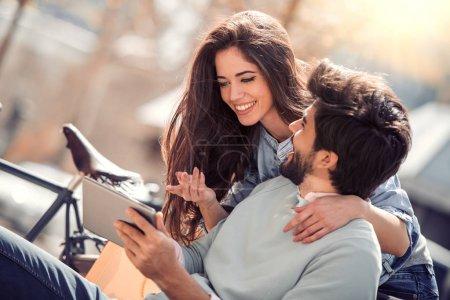 Couple utilisant une tablette numérique à l'extérieur, s'amuser ensemble .