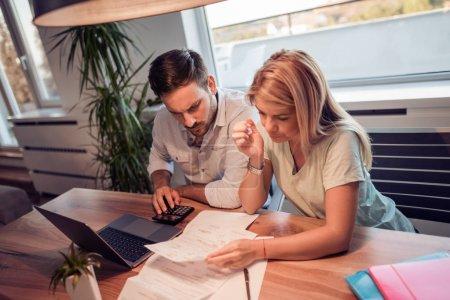Photo pour Femme et homme faire de la paperasse ensemble, paient des impôts en ligne sur ordinateur portable - image libre de droit