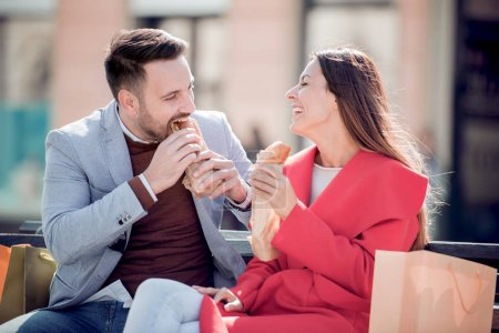 Photo for Couple sitting on bench and eating sandwich after shopping - Royalty Free Image