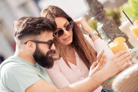 Man and woman dating in cafe and using smartphone