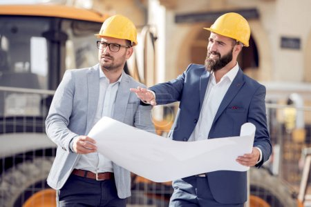 Photo for Engineer discussing project with colleague at construction site on sunny day - Royalty Free Image