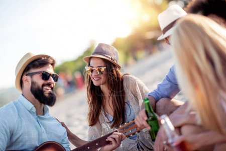 Photo for Group of friends playing guitar ,having fun and party on beach at sunset. - Royalty Free Image