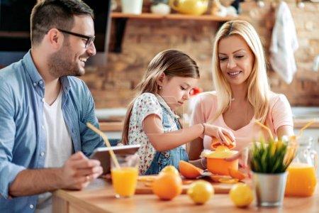 Photo pour Famille faire du jus dans leur cuisine et amusez-vous. Gens, amour, famille, concept de nourriture et de boisson. - image libre de droit