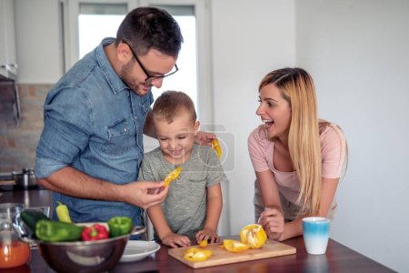 Photo for Happy young family preparing lunch in the kitchen and enjoying together. - Royalty Free Image