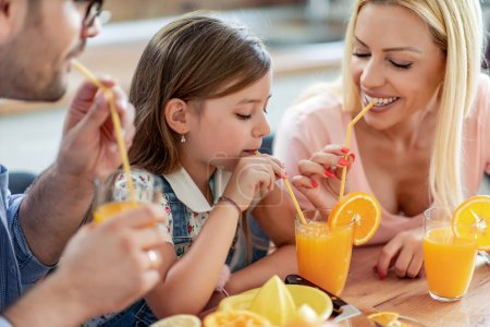 Photo for Family making juice in their kitchen and they drink fresh juice. People, love, family, food and drink concept. - Royalty Free Image