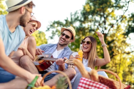 Photo for Summer, vacation, music and recreation time concept.Group of happy friends having fun outdoors with guitar. - Royalty Free Image