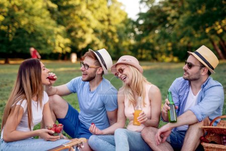 Photo for Happy friends in the park having picnic on a sunny day. - Royalty Free Image