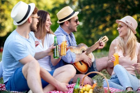 Photo for Happy group of friends having fun and smiling in the park.They play guitar. - Royalty Free Image