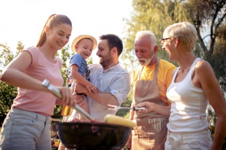 Photo for Happy big family gathered around the grill at picnic.Leisure,food,family and holidays concept. - Royalty Free Image