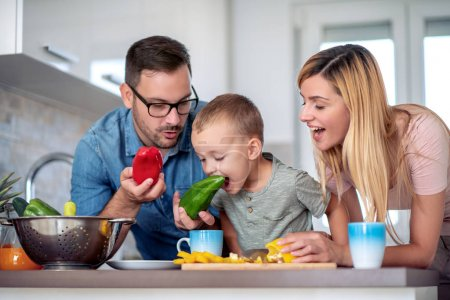 Photo for Cute little boy and his parents are cutting vegetables and smiling while making salad in kitchen. - Royalty Free Image