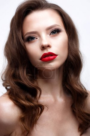 Photo for A young girl with a Hollywood wave and classic makeup. Beautiful model with red lips and arrows on eyes. Evening makeup and hairstyle. Beauty of the face.  White isolated background. Shining skin. - Royalty Free Image