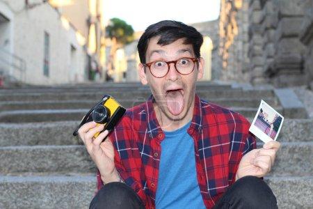 """Photo pour Portrait de près d'un beau jeune homme vêtu de vêtements élégants et d'une caméra de film d """"époque assis dans un escalier - image libre de droit"""