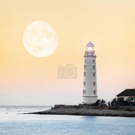 Photo for Lighthouse searchlight beam near ocean at sunset - Royalty Free Image