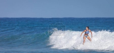 Surfer school. Beautiful young woman in swimsuit goes into ocean