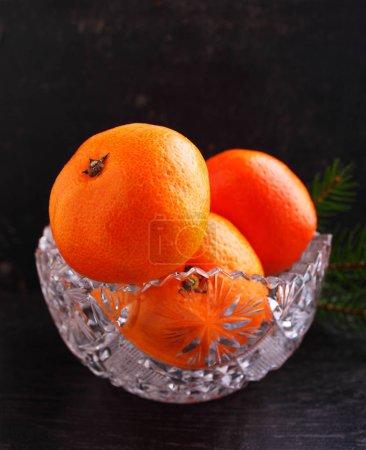 Photo pour Tangerines dans un vase en cristal sur fond noir . - image libre de droit