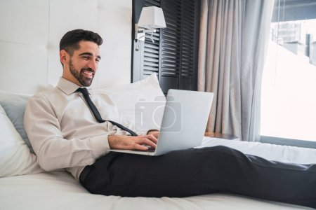 Portrait of young businessman lying on bed and wor...