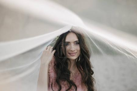 Young fiancee in wreath under veil