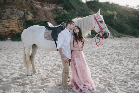 Young loving couple with white horse