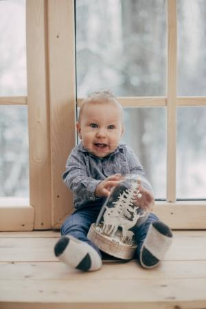 portrait of baby boy sitting with toy on wooden window sill