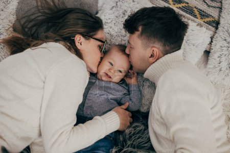 portrait of young couple kissing baby boy on bed
