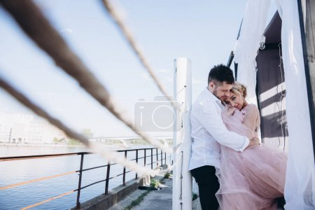 Photo for Portrait of hugging couple near railing on river shore - Royalty Free Image