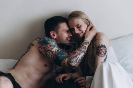 Sensual tattooed man embracing girl in bed
