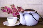 White teapot with white coffee cup on brick wall background and wooden table, retro style teapot, beautiful archidea flower.